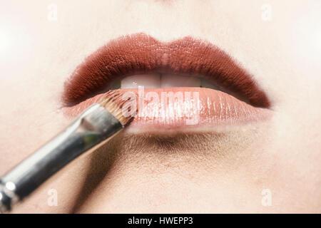 Nahaufnahme von Lippenstift auf junge Frau Lippe angewendet wird - Stockfoto