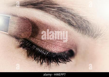 Nahaufnahme von Lidschatten auf junge Frau Augenlid angewendet wird - Stockfoto