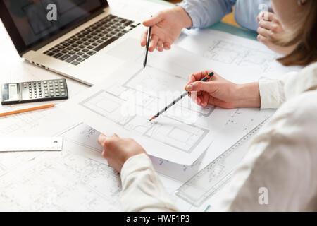 Junge weibliche Architekt und Designer arbeiten an Blueprint Projekt der neuen Wohnungen. Fotokonzept Arbeit auf technischen Zeichnungen