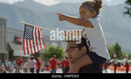 Patriotische Vater Tochter auf der Schulter tragen und Parade amerikanische Flagge winken - Stockfoto