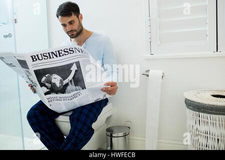 Mann sitzt auf WC-Sitz Lesen einer Zeitung zu Hause - Stockfoto