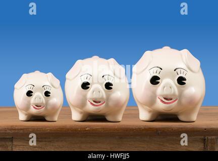Kleine mittlere und große Sparschweine auf Regal - Stockfoto
