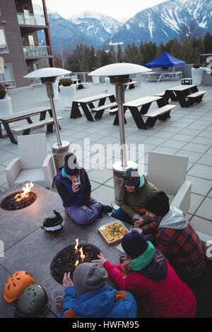 Gruppe von Skifahrern reiben sich die Hände in der Nähe von Kamin im Skigebiet - Stockfoto
