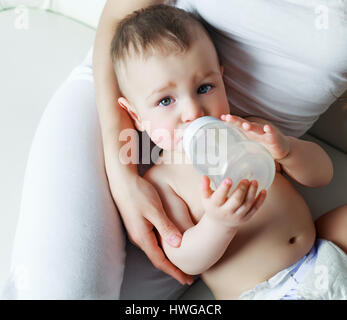 Mutter mit ihrem einjährigen Sohn Trinkwasser aus der Flasche - Stockfoto