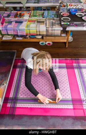 Drucken, drücken Holzschnitt mit Farbe auf Stoff, Frau Block fertig Gewebe an der Rückseite, Trolley mit verschiedenen Platten mit Farben