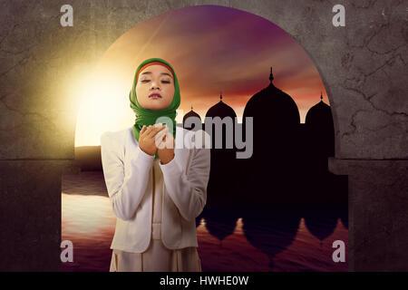 Asiatische Muslimin zu Gott beten. Sie trägt Hijab Inn Moschee. Sie beten zu Gott, sehr ernst - Stockfoto