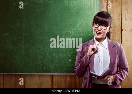 Asiatische Geschäftsfrau lächelnd über leere Tafel. Sie können Ihre Nachricht auf das Brett setzen. - Stockfoto
