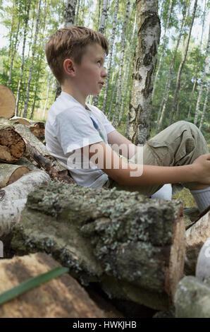 Junge ruht auf Haufen Brennholz Stämme, die er Stack im Alter von 10 Jahren half. Zawady Zentralpolen Europa - Stockfoto