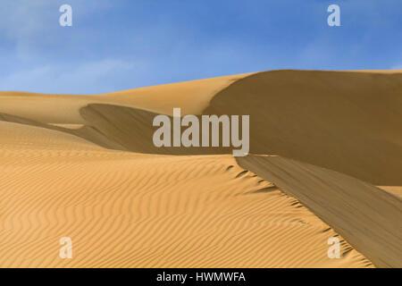 Minimalistische Fragment des gelben strukturierte Sanddünen unter blauem Himmel an einem sonnigen Tag. Wüstenhaften - Stockfoto