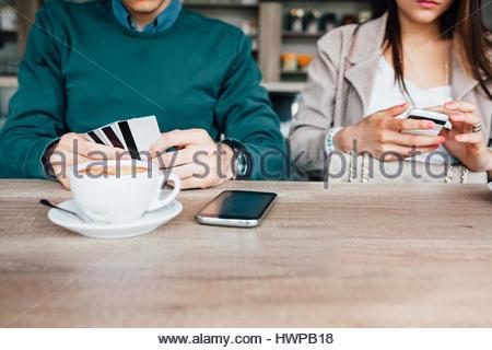 Man zahlt einen Kaffee mit Kredit-oder Bankkarte. Kopieren Sie auf Holztisch Platz. - Stockfoto