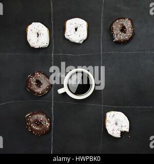 Tic Tac Toe Donuts und Kaffee über Schwarzes Brett Hintergrund. Bild von oben. - Stockfoto