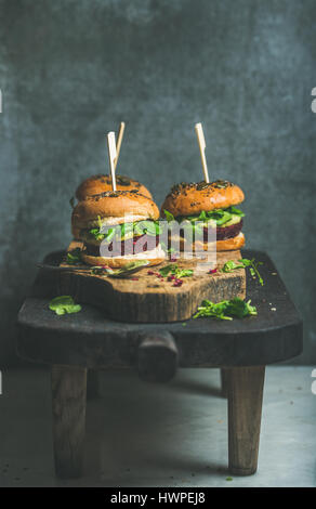 Gesunde vegane Burger mit rote Beete-Quinoa Patty und Rucola auf Tisch - Stockfoto