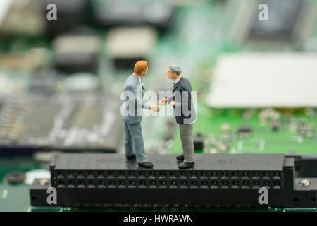 Vereinbarung zur wirtschaftlichen Zusammenarbeit von zwei Mini Geschäftsmann Shake Hand auf Mainboard Hintergrund - Stockfoto