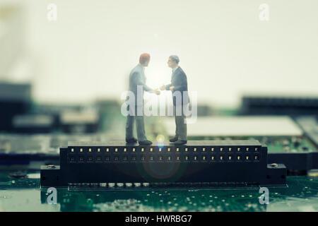 zwei Mini-Geschäftsmann Shake Hand auf Stand auf Mainboard für Make eine Einigung über Effekt leichte Kost - können - Stockfoto