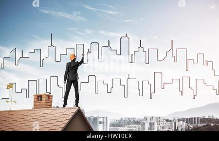 Mann Architekten zeichnen Silhouette der modernen Stadt am blauen Himmel. Gemischt - Stockfoto