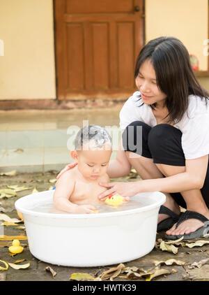 Asiatisches Baby Junge war Baden und Shampoonieren von Mutter in der weißen Wanne. Er spielt voller Glück, Seite - Stockfoto