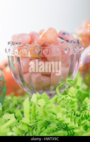 Ostereier und Jelly Beans in einem Glasbehälter und auf grünem Krepp-Papier - Stockfoto