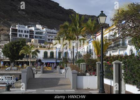 Weiße Häuser, Palmen, Blumen blühen in den Abendstunden. Blick auf die Straße, Puerto de Mogan, Gran Canaria, Spanien. - Stockfoto