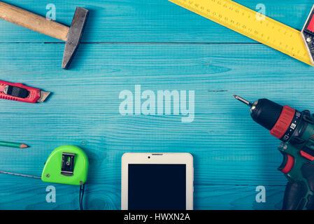 Tinker Toools auf der grünen Holzoberfläche und Tablet Website angezeigt. DIY-Konzept. - Stockfoto