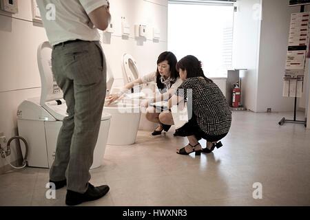 Eine Dame präsentiert die Elemente einer modernen japanischen Toilette, Japan. - Stockfoto