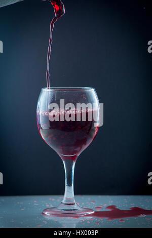 helle schöne rote Wein eingießen Jet in eine transparente Glastasse auf einem dunklen Hintergrund isoliert - Stockfoto