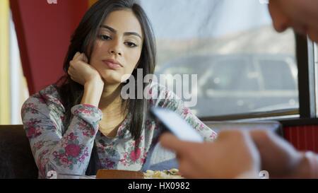 Selektiven Fokus Überblick darüber verärgert Freundin mit abgelenkt Freund mit Smartphone am Tisch im café - Stockfoto
