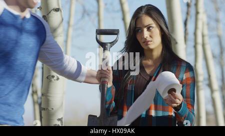 Niedrigen Winkel Blick auf Freund trösten verärgert Freundin mit Toilettenpapier und Schaufel in abgelegenen Wäldern - Stockfoto