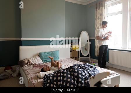 Kleiner Junge auf seines Vaters Bett wälzen, durch das Fenster hält seinen Sohn verärgert Baby steht - Stockfoto