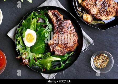 Grüner Salat und gegrilltes Schweinefleisch Steak auf dem Teller auf dunklem Hintergrund, Ansicht von oben - Stockfoto