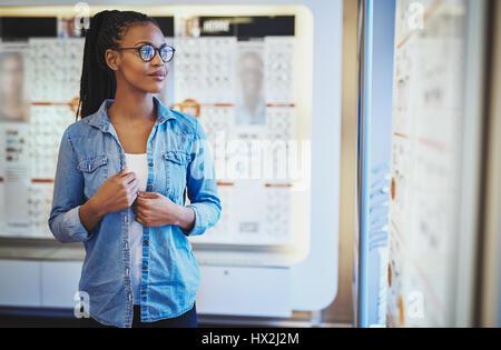 Single grinsend ruhige Schwarze Frau in Brillen mit beiden Händen am Shirt beim Stehen vor der Anzeige an eye Wear - Stockfoto