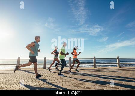 Gruppe von Athleten auf Meerseite. Läufer in Sportbekleidung zusammen im Freien zu trainieren. - Stockfoto