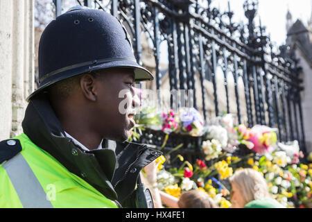 London, UK. 25. März 2017. Ein junger Polizist steht Wache vor den Toren von den Houses of Parliament. Nach der - Stockfoto