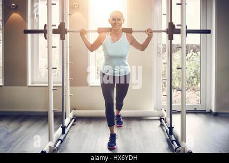 Junge Frau in Sportkleidung in der Turnhalle mit Langhantel stehend, Blick in die Kamera und lächelnd dabei Longe - Stockfoto