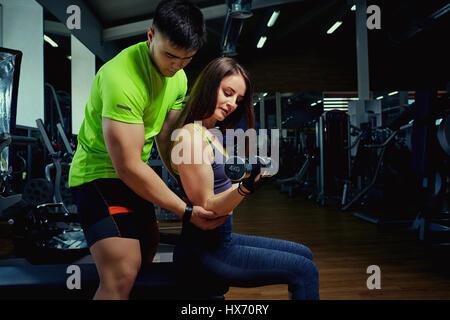 Persönlicher Trainer hilft einem Mädchen Heben von Gewichten im Fitnessstudio - Stockfoto