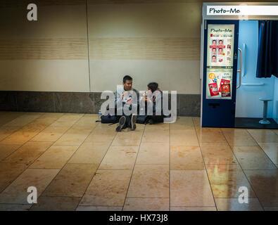 zwei Personen Essen am Boden neben einem Foto-mich schnellen Fotoautomaten in einem Einkaufszentrum in Cambridge - Stockfoto