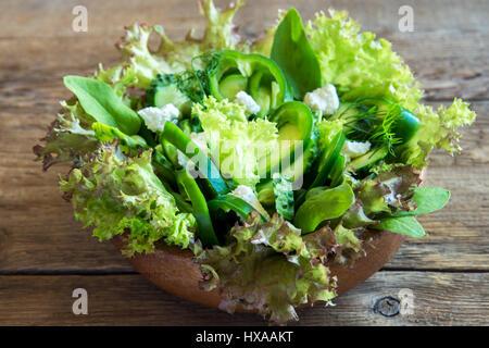 Bio grüner Gemüsesalat mit Feta-Käse gemischt und Frühjahr Erbsen in Holzschale hautnah - gesunde Ernährung Bio Vegan vegetarisch Essen Mahlzeit Salat