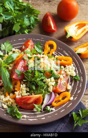 Tomaten-Couscous-Salat mit Gemüse und grünen - gesunde vegetarische vegane Gemüse Bio Diät Salat essen über rustikalen - Stockfoto