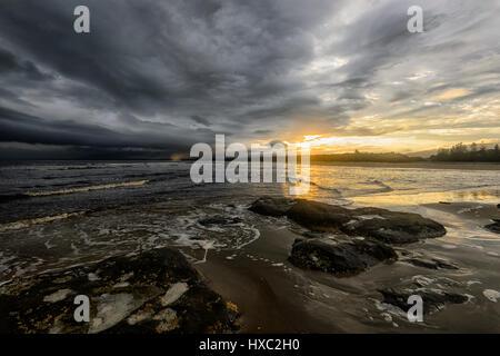 Dramatischen Sonnenuntergang mit schwarzen bedrohlichen Wolken über Seven Mile Beach, Gerroa, Illawarra Coast, New - Stockfoto