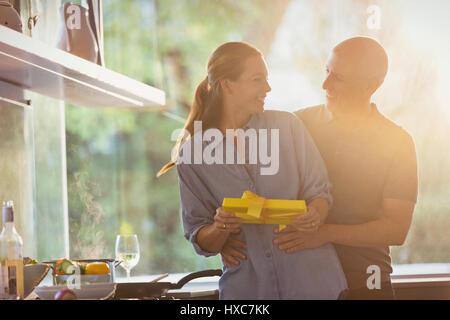 Lächelnder Mann überraschend Frau mit Geschenk in sonnige Küche - Stockfoto