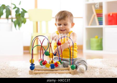 Kind Junge spielt mit pädagogisches Spielzeug drinnen - Stockfoto
