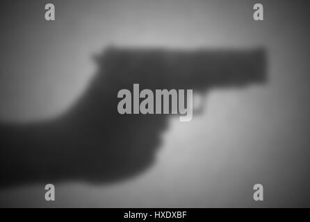 Silhouette hinter einem Transparentpapier - unscharf - Handfeuerwaffe - Stockfoto