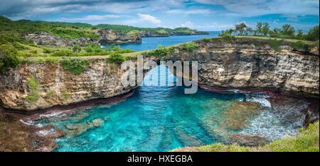 Stein Bogen über dem Meer. Gebrochene Strand, Nusa Penida, Indonesien. - Stockfoto