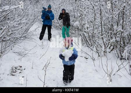 Mädchen hält Schneeball mit Familie im Hintergrund an schönen verschneiten Tag - Stockfoto