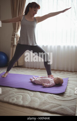 Glückliche Mutter tun Krieger-Pose beim betrachten Baby im Haus - Stockfoto