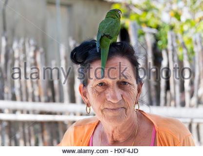 Kubanische Bäuerin mit kleiner Papagei Haustier. Realen Person Tiere Vogel Maskottchen zu genießen. - Stockfoto