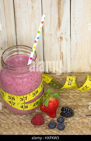 rosa Beeren-Smoothie im Einmachglas mit Polka Dot Stroh und gelben Maßband - Stockfoto