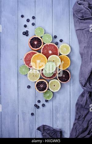 Vielzahl von Zitrusfrüchte (Orange, Blutorangen, Zitronen, Grapefruit und Limetten) mit Heidelbeeren mit grauem Stoff über einen blauen rustikale Holz Tischplatte. Stockfoto