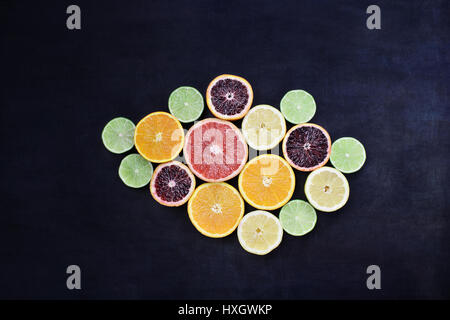 Vielzahl von Zitrusfrüchte (Orange, Blutorangen, Zitronen, Grapefruit und Limetten) über einem schwarzen rustikalen Hintergrund. Bild von oben. Stockfoto