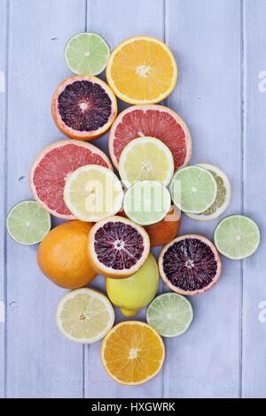 Vielzahl von Zitrusfrüchte (Orange, Blutorangen, Zitronen, Grapefruit und Limetten) über einen blauen Holz Tischplatte rustikal Hintergrund. Bild von overhea Stockfoto