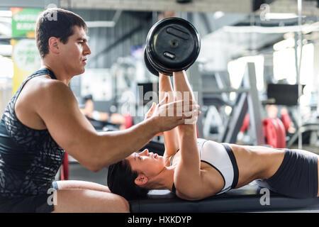 Lehrer helfen Frau im Fitness-Studio - Stockfoto